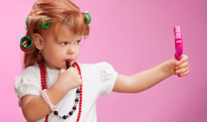 Little girl playing with mothers makeup and holding mirror on pink background